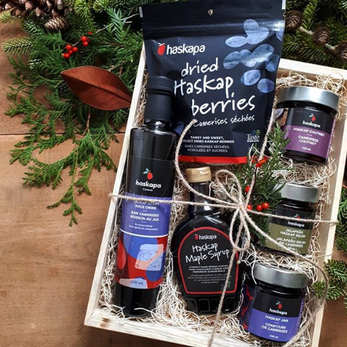 Haskapa gift crate tied with a bow and surrounded by Christmas tree branches and pinecones