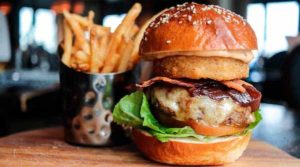 Burger and fries sitting on cutting board